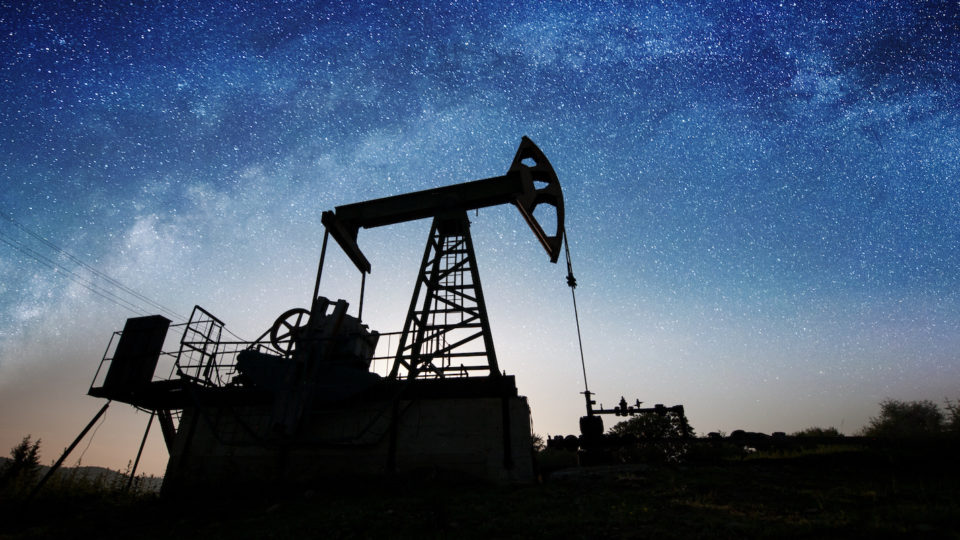 Silhouette of oil pump jack pumping on the oil field in the night with starry sky galaxy. Milky way. Oil industry equipment